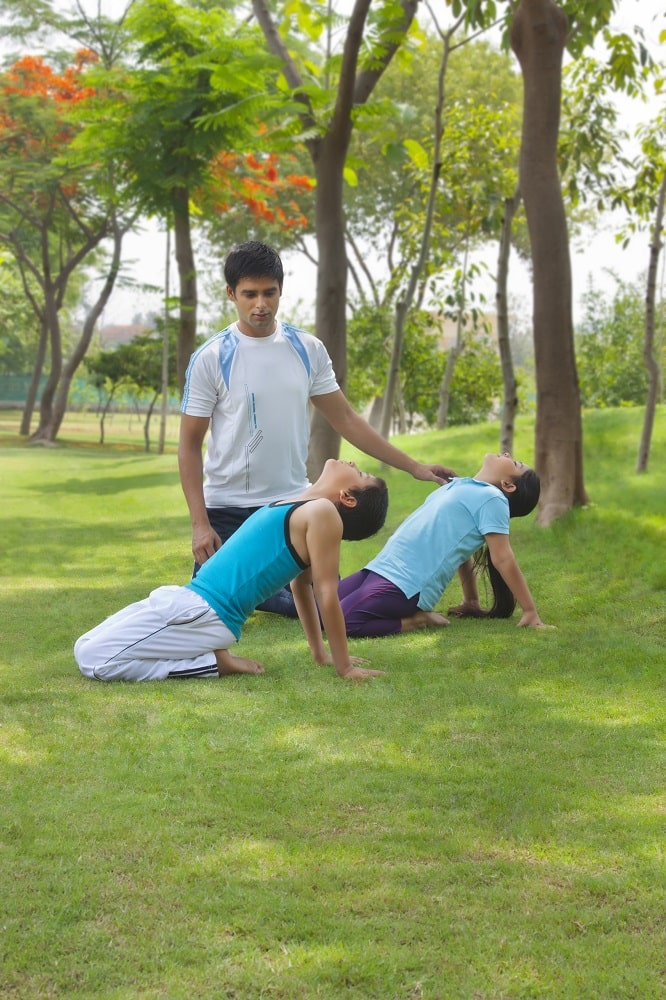 A male yoga instructor assisting two students maintain the proper form during a private yoga session outdoors.