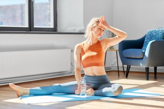A woman with her hand on her forehead and the other holding a water bottle, feeling tired rather than energized after her yoga session.