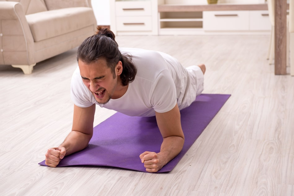 A man doing Plank Pose for his yoga session, stretching his capability even in pain.
