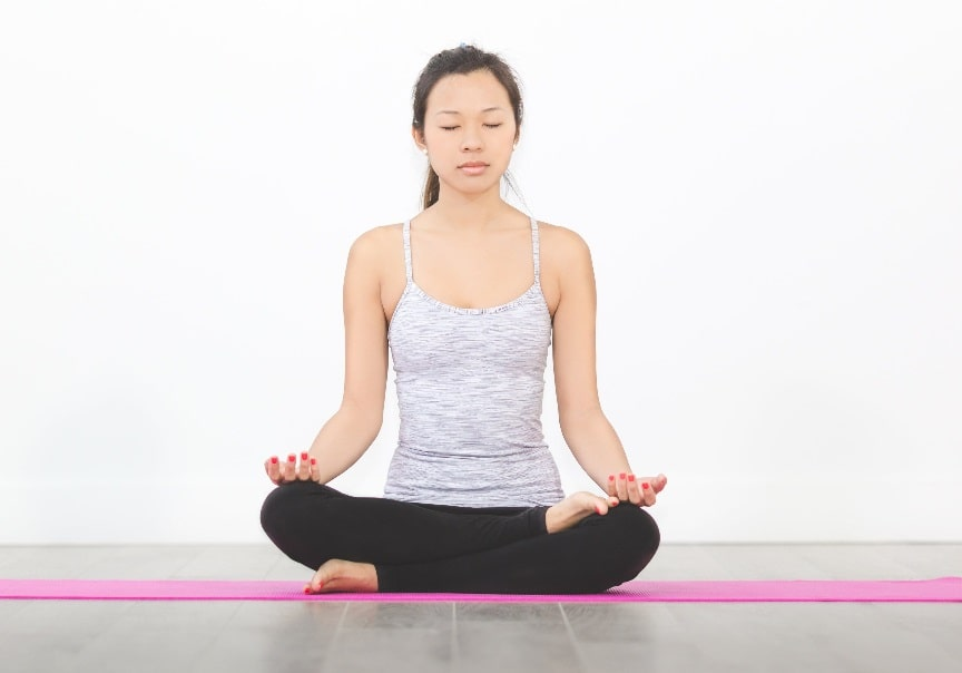 A woman doing Lotus Pose to improve her posture for her herniated disc.