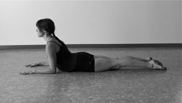A black and white photo of a woman doing Sphinx Pose to strengthen her back for her herniated disc.