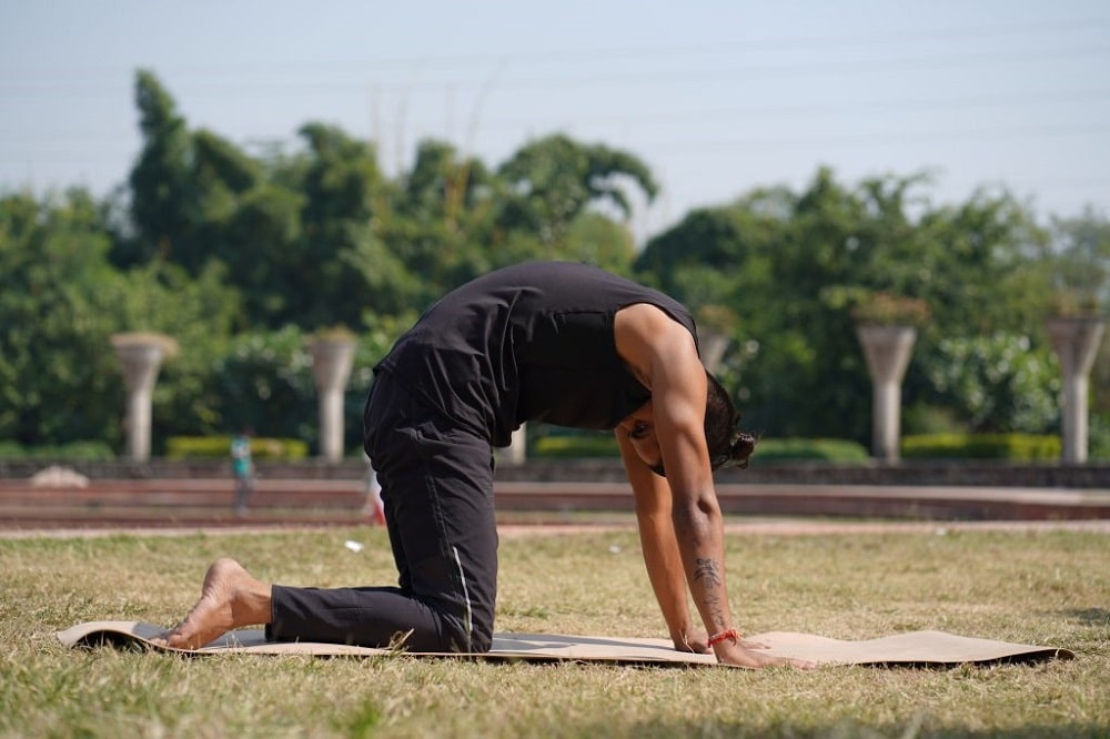 A male yoga practitioner doing Cat-Cow Pose for his outdoor yoga session to alleviate back pain due to a herniated disc.