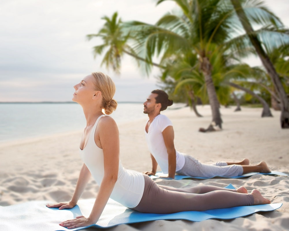 A man and a woman doing Sphinx Pose for their beach yoga session to strengthen their core, relieve back pain, and improve mobility for treating disc herniation.